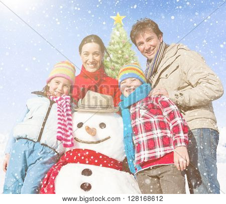 Family standing around snowman and a christmas tree behind them.