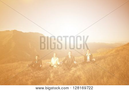 Concept of business people meditating on the mountains.