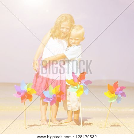 Summer kids embracing on a tropical beach. Environmental conservation concept.Young family enjoying their summer vacation.