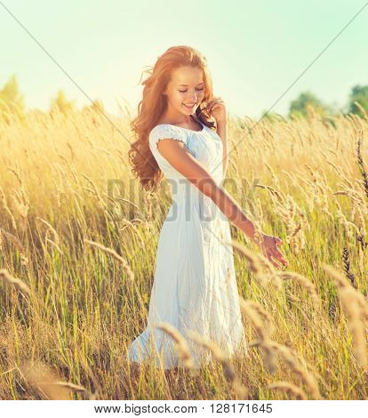 Beauty Girl Outdoors enjoying nature. Beautiful Teenage Model girl with perfect long curly hair, in white dress standing on the Spring Field, Raising hands in Sun Light