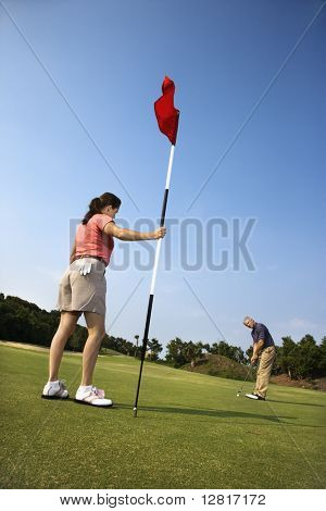 Caucasion mid-adult man putting golfball while Caucasion mid-adult woman holds flag.