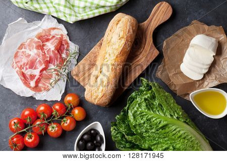 Ciabatta sandwich cooking with romaine salad, prosciutto and mozzarella cheese over stone background. Top view