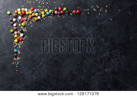 Colorful candies on stone background. Top view with copy space