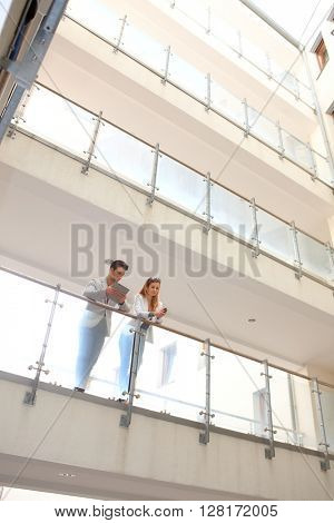 Young businesspeople talking in balcony of modern building.