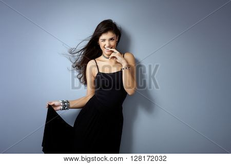 Sexy girl posing by grey wall, winking, biting finger impish.
