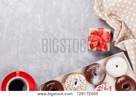 Colorful donuts, gift box and coffee on stone table. Top view with copy space