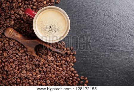 Coffee cup and beans on stone table. Top view with copy space