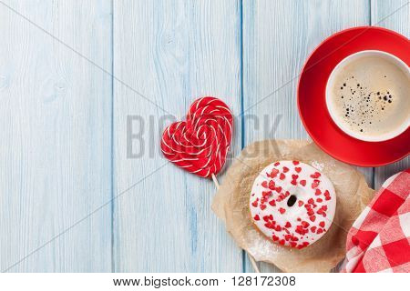 Donut, heart shaped candy and coffee on wooden table. Top view with copy space