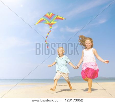 Sister and brother playing with kite on beach.