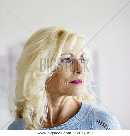 Portrait of tan blonde Caucasion middle-aged woman wearing lots of makeup.