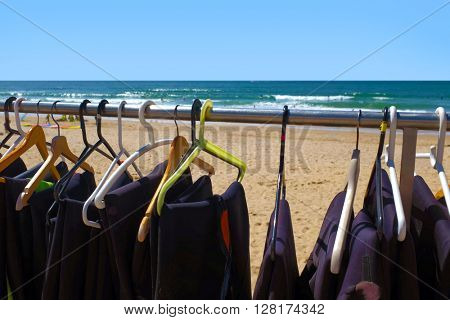 Row of surfing wet suits on hangers drying under the sun at the beach