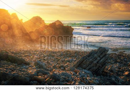 Seascape with sun beams at sunset in Abano Beach, Portugal.
