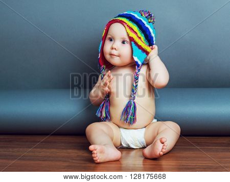 adorable baby wearing diapers and a warm winter hat