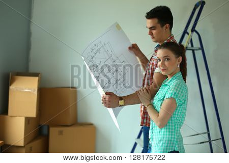 Portrait of young couple moving in new home with plane