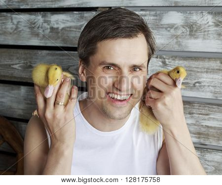 young handsome farmer with two ducklings against wooden wall