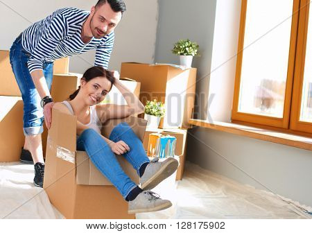 Happy couple having fun and riding in cardboard boxes at new home
