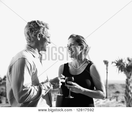 Black and white image of mid-adult Caucasian couple holding wine glasses and smiling at each other.