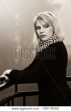 Young woman leaning on handrail outdoor. Female fashion model in black coat