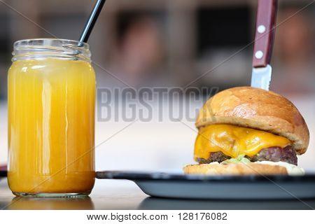 Cheeseburger and lemonade in jar on table