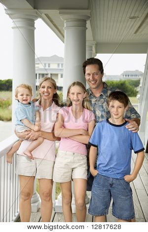 Family portrait of Caucasian mid-adult man and woman with pre-teen girl and boy and male toddler, standing on porch.