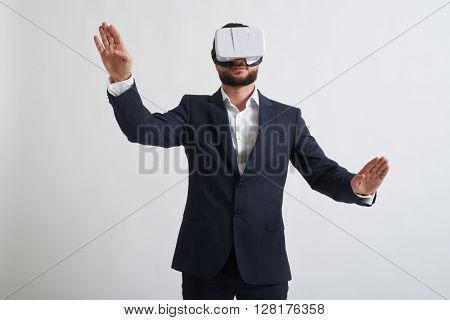 Close up of businessman in a formal wear who trying to push something wearing virtual reality glasses