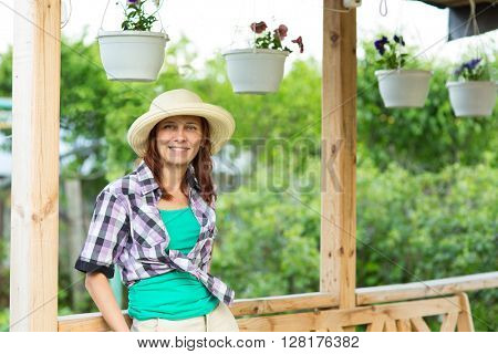 young woman standing in the gazebo in his garden