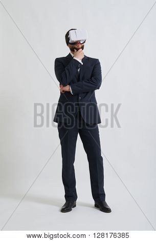 Businessman in a formal wear and virtual reality glasses thinking about something