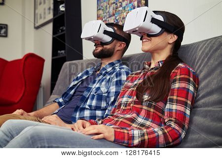 A young man and woman in casual clothes and virtual reality glasses is watching something