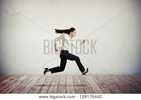 Young pretty serious woman in formal wear running and jumping