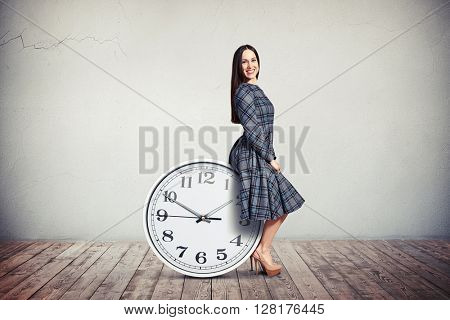 A young smiling woman in checkered dress is sitting on a big round clock on the wooden floor