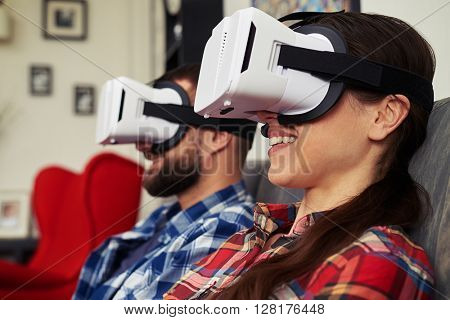 Close up of young man and woman in casual clothes and virtual reality glasses that watching something