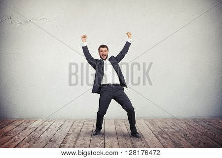 A young man in grey business suit is vigorous and joyful apparently he succeeded in something