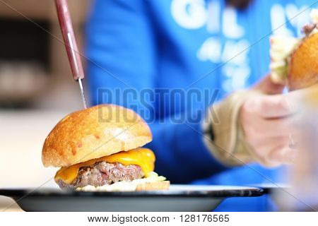 Cheeseburger on table with shallow depth of field, woman in background eating another one
