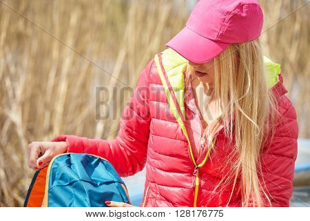 young woman with backpack standing on shore and enjoying of lake view.