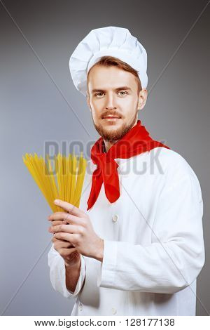 Male chef cook holding uncooked spaghetti. Occupations. Studio shot.