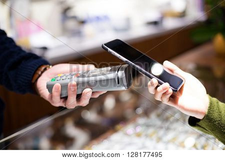 Woman using NFC technology to make payment