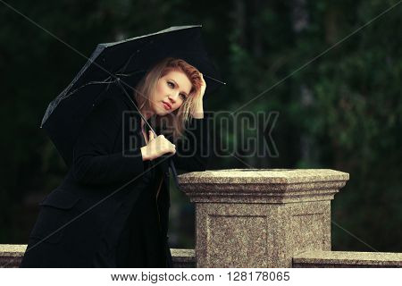 Sad young woman with umbrella in the rain. Female fashion model in classic black coat outdoor