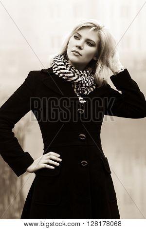 Young woman in black coat walking outdoor. Female fashion model