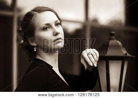 Sad beautiful fashion woman in black dress on city street. Female fashion model outdoor