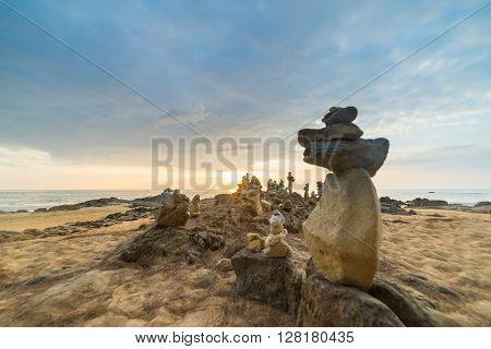 Stones pyramid on sand symbolizing zen, harmony, balance. Ocean at sunset in Khao Lak Thailand