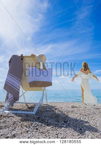 WOman with sun lounger chair on the beach - Focused on the chair