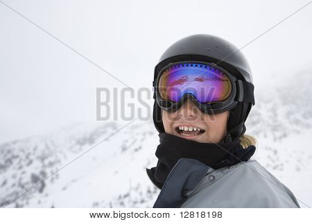 Caucasian teenage boy skier in helmet and goggles at ski resort on mountain in Whistler, British Columbia, Canada.