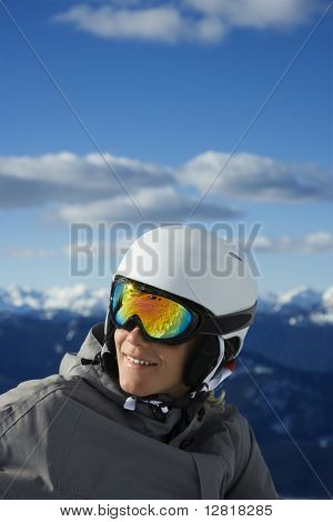 Caucasian teenage boy  snowboarder wearing helmet and goggles on mountain Whistler, British Columbia, Canada.
