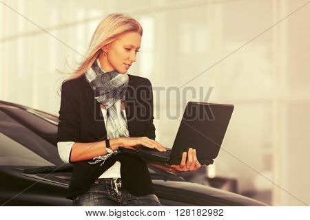 Young fashion business woman with laptop standing next to her car. Female blond fashion model in black jacket outdoor