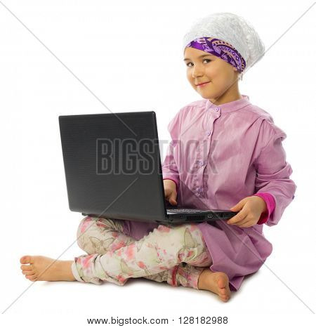 Little girl in traditional muslim clothes with laptop isolated