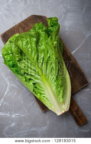 Green salad leaves. Green Romano leaves on wooden cutting board. Fresh lettuce on kitchen table. Healthy organic food