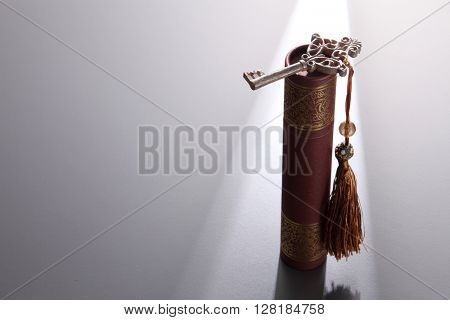 round certificate holder, certificate and key with tassel on the black background