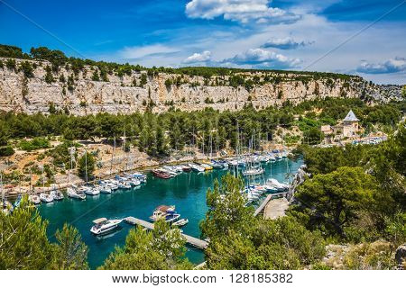 The picturesque fjord with turquoise water at coast of the Mediterranean Sea.park of Calanques in Provence, between Marseille and Kassis.  White and graceful sailing yachts in the deep sea gulf