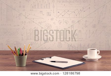Close up of white business office desk with laptop tablet in front of brown wall background full of pie charts and numbers