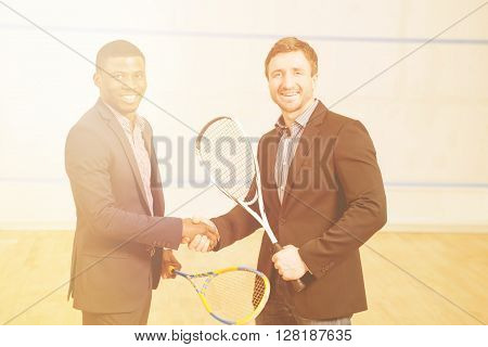 Happy businessmen holding rackets and shaking hands before having big match in squash on squash court.